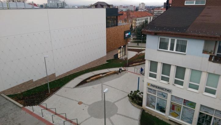 """Budova v tvare """"L"""" zviera """"parkovú úpravu, zväčša sú je to len dlažba a lavičky"""